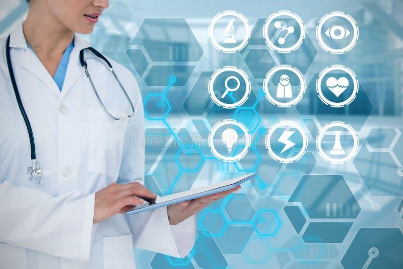 Zusammengesetztes Bild glücklichen Doktors, der ihren Tabletten-PC verwendet lizenzfreie stockfotografie