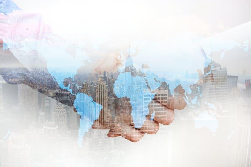 Zusammengesetztes Bild mit den Geschäftsleuten, die Hände und Stadtwolkenkratzer rütteln stockbilder