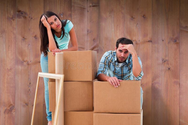 Zusammengesetztes Bild von betonten jungen Paaren mit beweglichen Kästen lizenzfreies stockbild