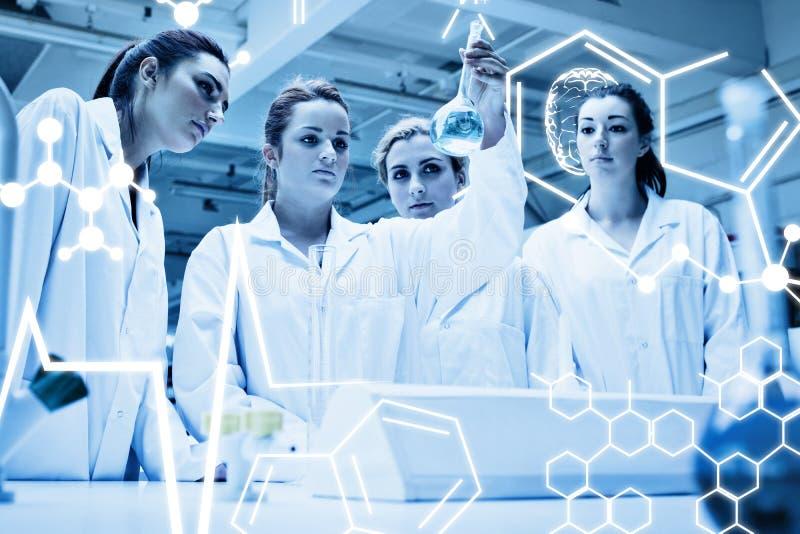 Zusammengesetztes Bild von den Chemiestudenten, die eine Flüssigkeit betrachten lizenzfreie abbildung