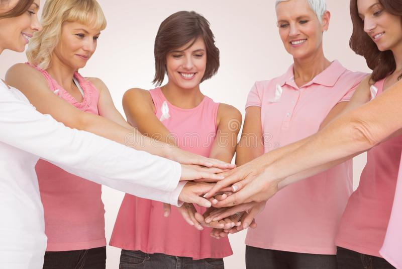 Zusammengesetztes Bild von den Freundinnen, die Hände für Brustkrebsbewusstsein stapeln lizenzfreie stockfotografie