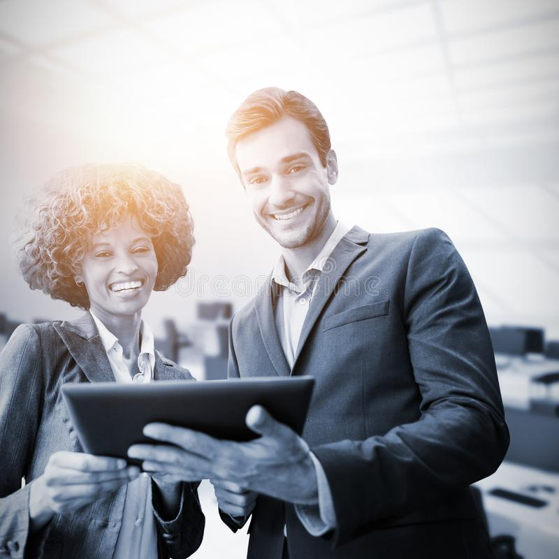 Zusammengesetztes Bild von den Geschäftsleuten, die mit einer Tablette stehen stockbilder