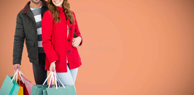 Zusammengesetztes Bild von den glücklichen jungen Paaren, die Einkaufstaschen halten lizenzfreies stockfoto