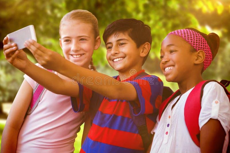 Zusammengesetztes Bild von den glücklichen Kindern, die selfie im Schulkorridor nehmen lizenzfreies stockbild