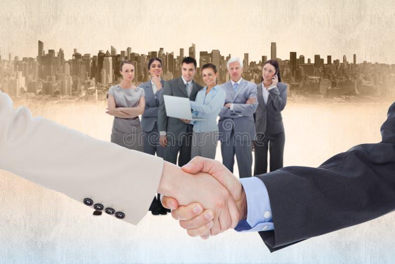 Zusammengesetztes Bild von den lächelnden Geschäftsleuten, die Hände beim Betrachten der Kamera rütteln stockbild