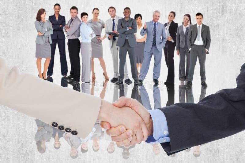 Zusammengesetztes Bild von den lächelnden Geschäftsleuten, die Hände beim Betrachten der Kamera rütteln lizenzfreie stockfotografie