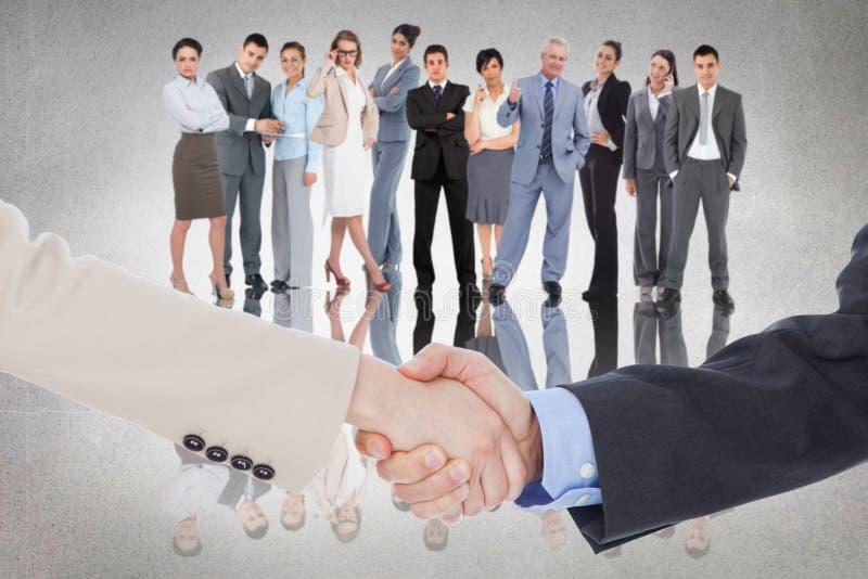 Zusammengesetztes Bild von den lächelnden Geschäftsleuten, die Hände beim Betrachten der Kamera rütteln lizenzfreie stockfotos
