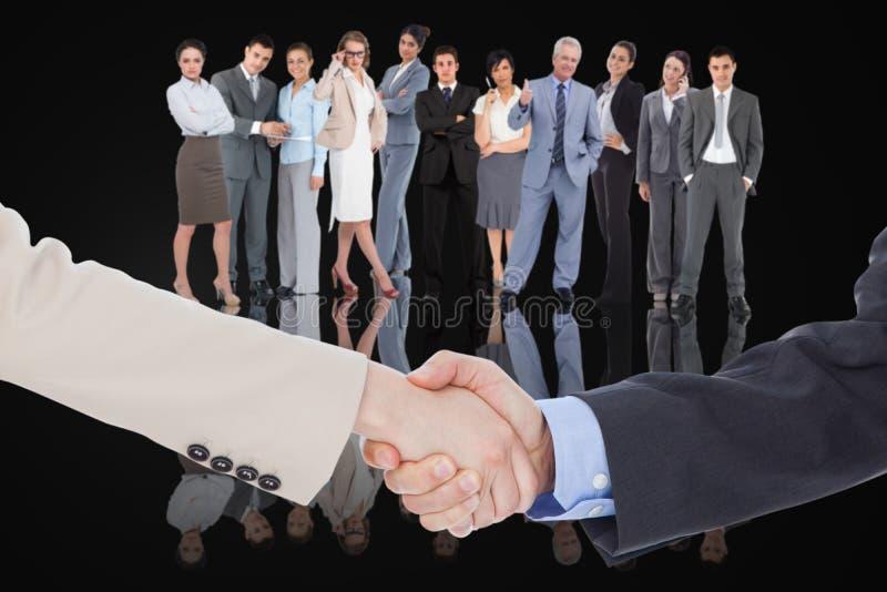 Zusammengesetztes Bild von den lächelnden Geschäftsleuten, die Hände rütteln stockbild