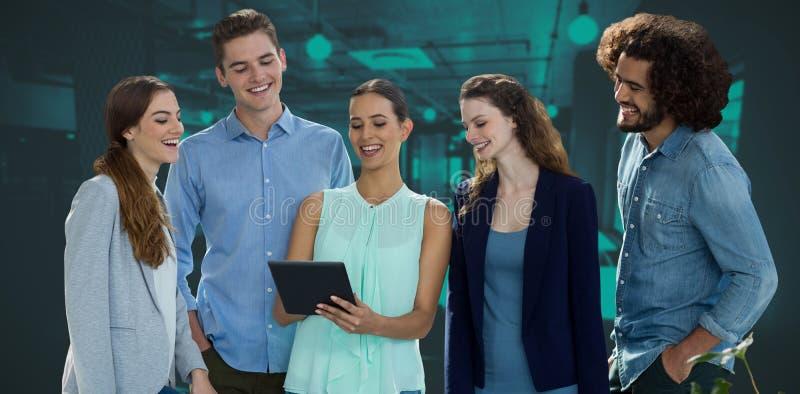 Zusammengesetztes Bild von den lächelnden Kollegen, die über digitaler Tablette bei der Stellung gegen weißes Ba sich besprechen stockbilder
