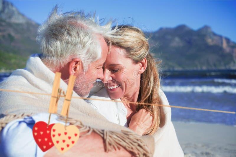 Zusammengesetztes Bild von den lächelnden Paaren, die auf dem Strand unter Decke sitzen lizenzfreie abbildung