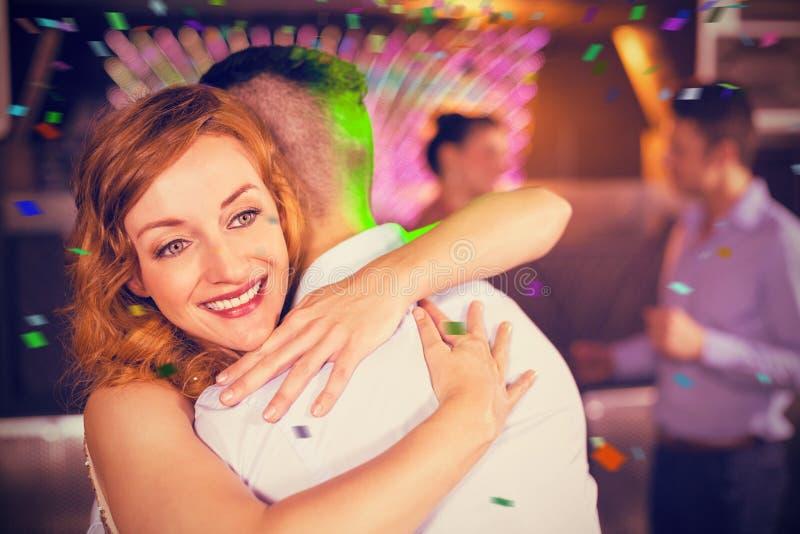 Zusammengesetztes Bild von den lächelnden Paaren, die in der Stange sich umfassen lizenzfreie stockfotografie