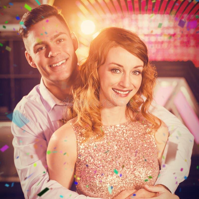 Zusammengesetztes Bild von den lächelnden Paaren, die in der Stange sich umfassen lizenzfreies stockfoto