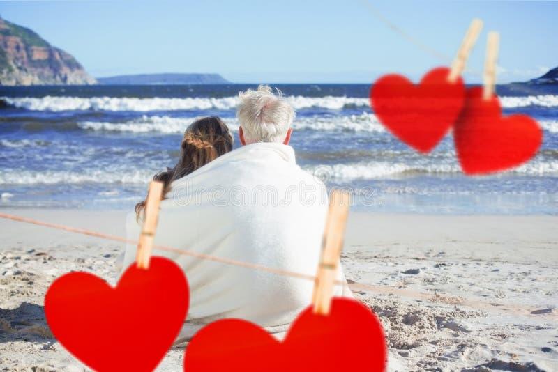 Zusammengesetztes Bild von den Paaren, die auf dem Strand unter der Decke heraus schaut zum Meer sitzen vektor abbildung