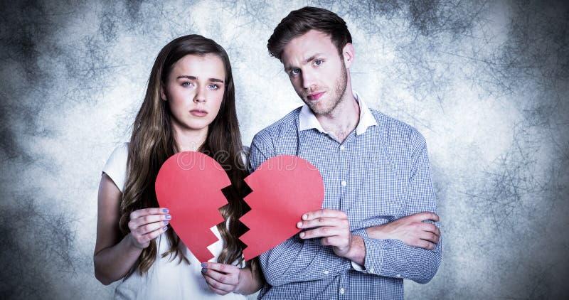 Zusammengesetztes Bild von den Paaren, die defektes Herz halten lizenzfreies stockbild