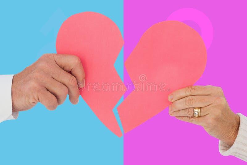 Zusammengesetztes Bild von den Paaren, die ein defektes Papierherz halten lizenzfreie stockbilder