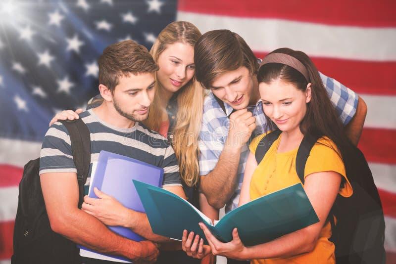Zusammengesetztes Bild von den Studenten, die Ordner am Collegekorridor halten lizenzfreie stockfotografie