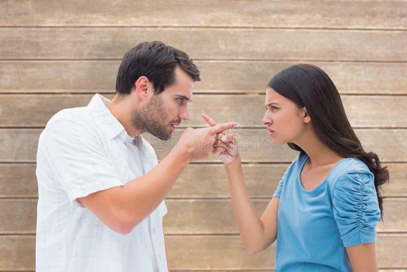 Zusammengesetztes Bild von den verärgerten Paaren, die auf einander zeigen lizenzfreie stockfotografie