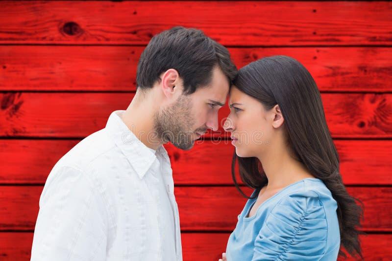 Zusammengesetztes Bild von den verärgerten Paaren, die entlang einander anstarren lizenzfreies stockbild