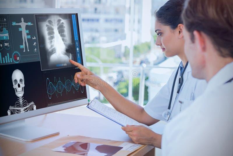 Zusammengesetztes Bild von Doktor zeigend auf den Schirm eines Computers stockbild
