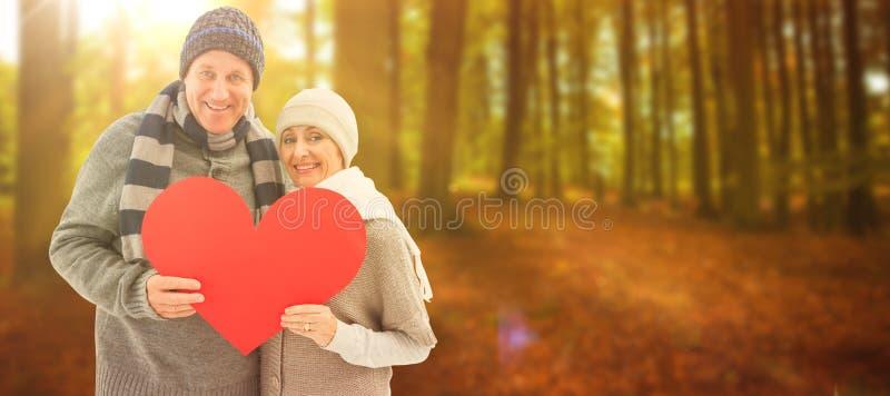 Zusammengesetztes Bild von glücklichen reifen Paaren im Winter kleidet das Halten des roten Herzens stockfoto