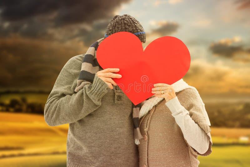Zusammengesetztes Bild von glücklichen reifen Paaren im Winter kleidet das Halten des roten Herzens stockfotografie