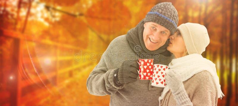 Zusammengesetztes Bild von glücklichen reifen Paaren im Winter kleidet das Halten von Bechern lizenzfreies stockfoto