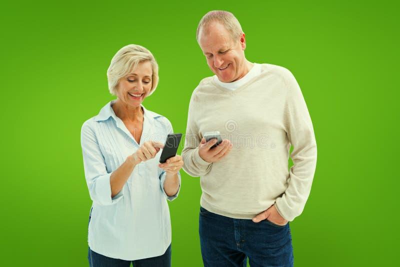 Zusammengesetztes Bild von glücklichen reifen Paaren unter Verwendung ihrer Smartphones lizenzfreie stockfotos
