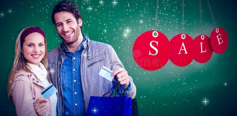 Zusammengesetztes Bild von lächelnden Paaren mit den Einkaufstaschen, die Kreditkarte zeigen stockbild