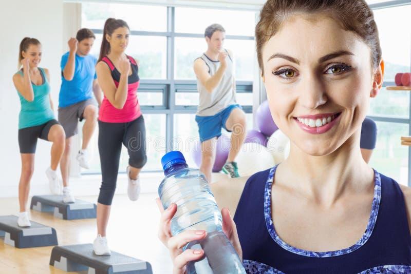 Zusammengesetztes Bild von Sitz Brunette Wasserflasche halten lizenzfreie stockfotos