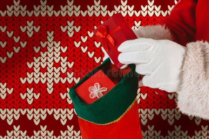 Zusammengesetztes Bild von Weihnachtsmann Geschenke in Weihnachtsstrümpfe einsetzend stockfoto