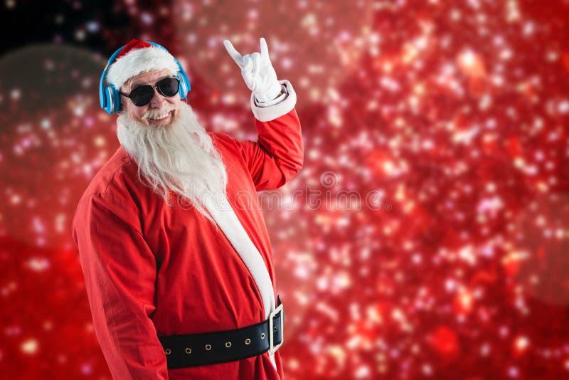 Zusammengesetztes Bild von Weihnachtsmann Hand-yo Zeichen beim Hören zeigend Musik auf Kopfhörern stockfoto