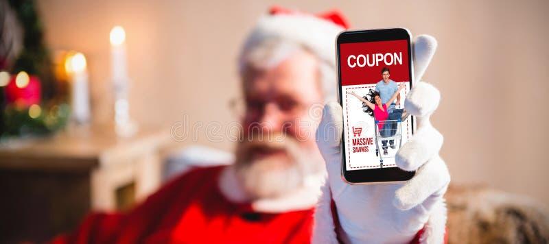 Zusammengesetztes Bild von Weihnachtsmann seinen Smartphone sitzend und zeigend stockbild