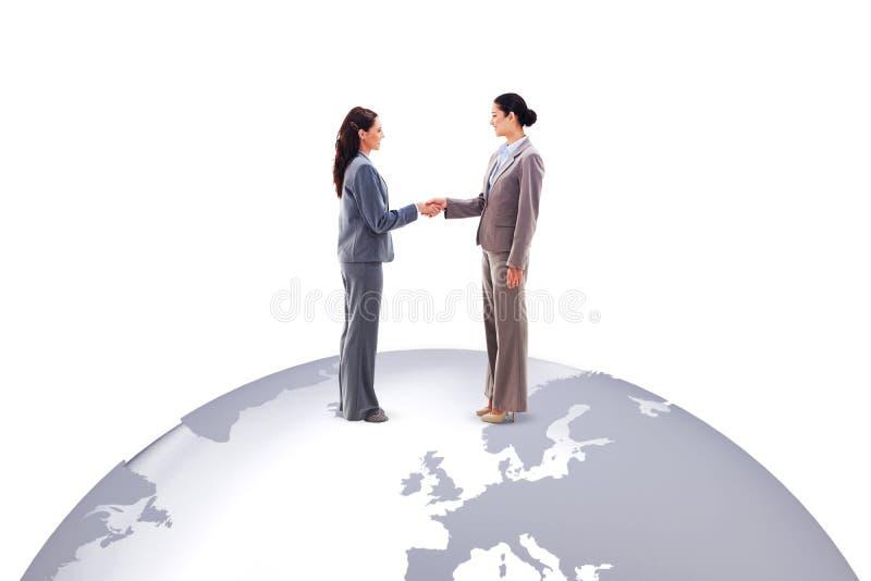 Zusammengesetztes Bild von zwei Geschäftsfrauen, die Hände rütteln stockfoto