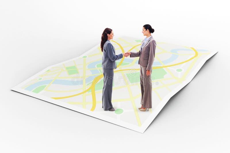 Zusammengesetztes Bild von zwei Geschäftsfrauen, die Hände rütteln lizenzfreie stockfotos