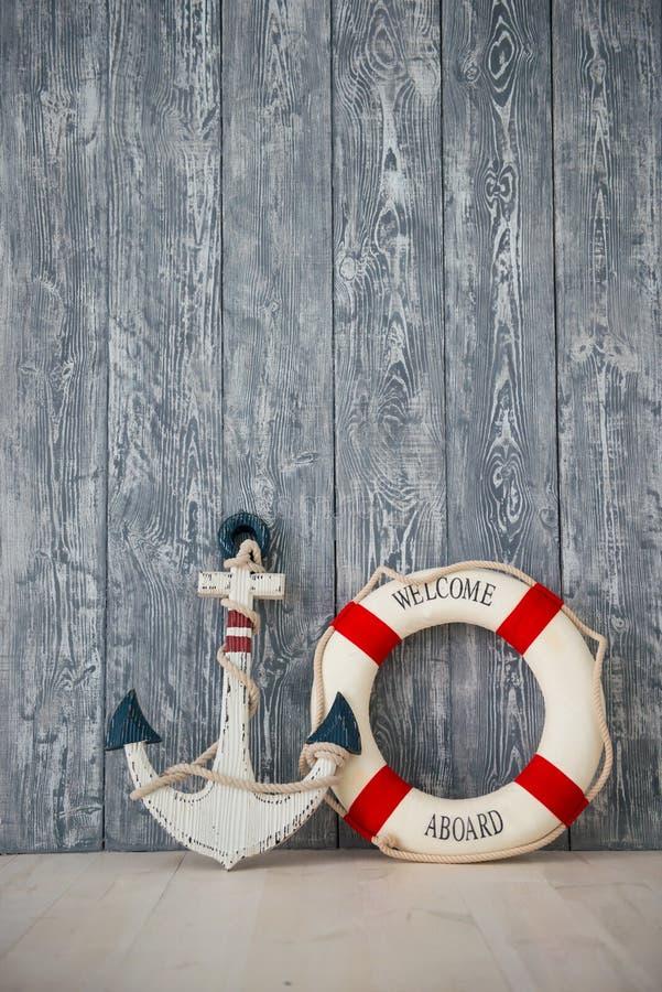Zusammensetzung auf dem Marinethema mit Anker und Rettungsleine auf hölzernem Hintergrund stockfotos