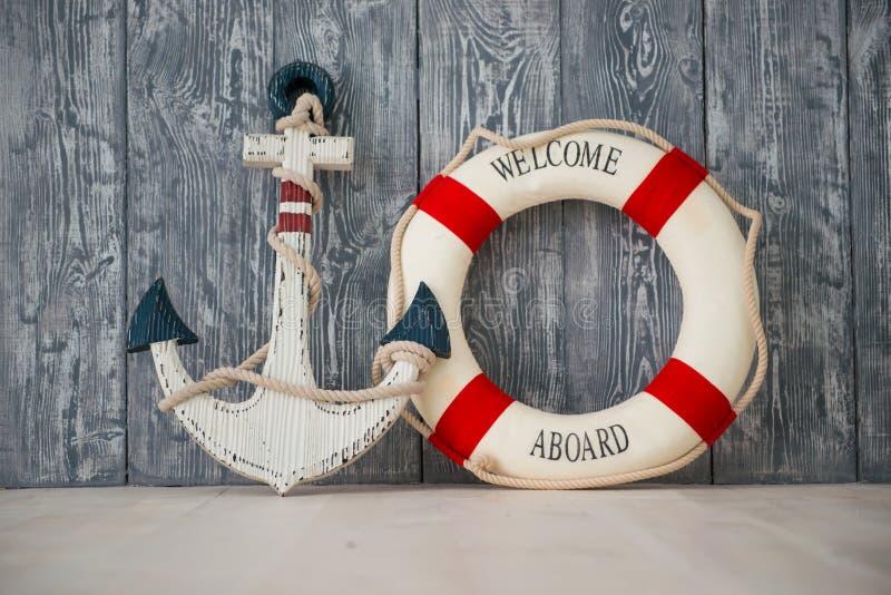 Zusammensetzung auf dem Marinethema mit Anker und Rettungsleine auf hölzernem Hintergrund stockfotografie