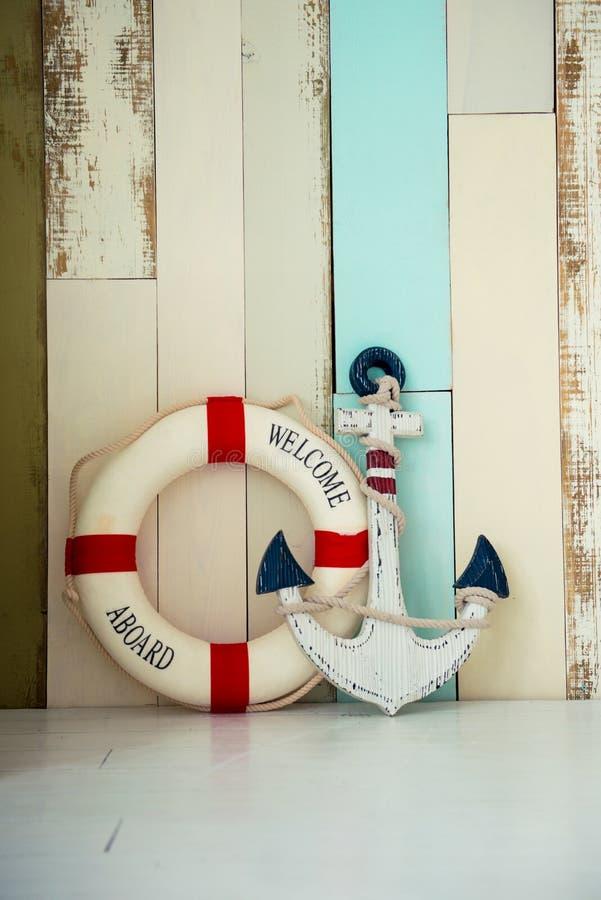 Zusammensetzung auf dem Marinethema mit Anker und Rettungsleine auf hölzernem Hintergrund lizenzfreie stockbilder