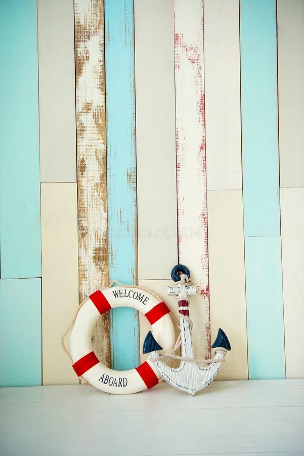 Zusammensetzung auf dem Marinethema mit Anker und Rettungsleine auf hölzernem Hintergrund stockfoto