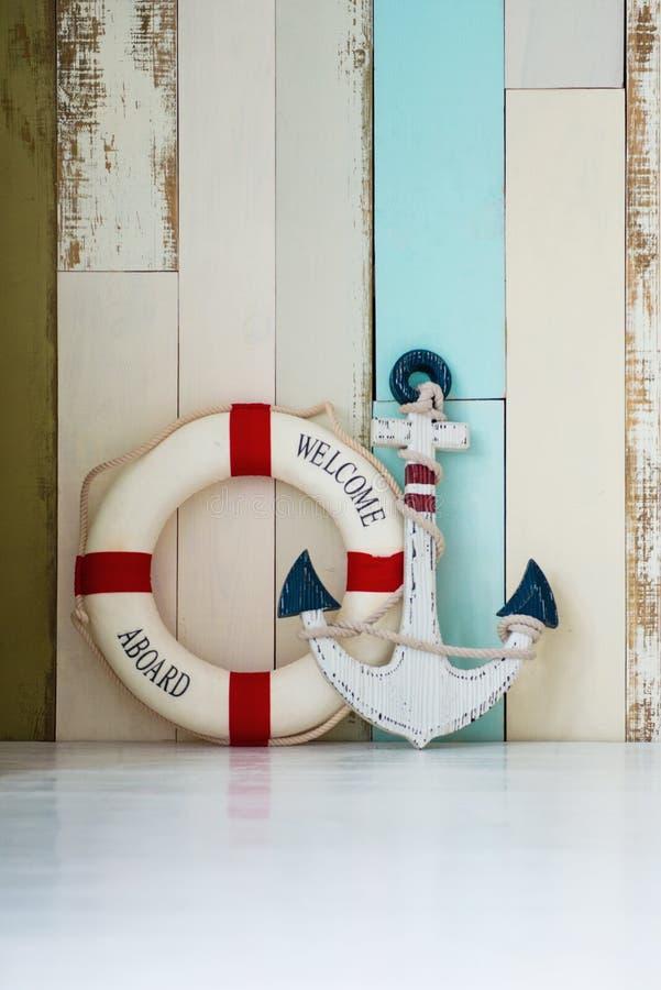 Zusammensetzung auf dem Marinethema mit Anker und Rettungsleine auf hölzernem Hintergrund stockbilder