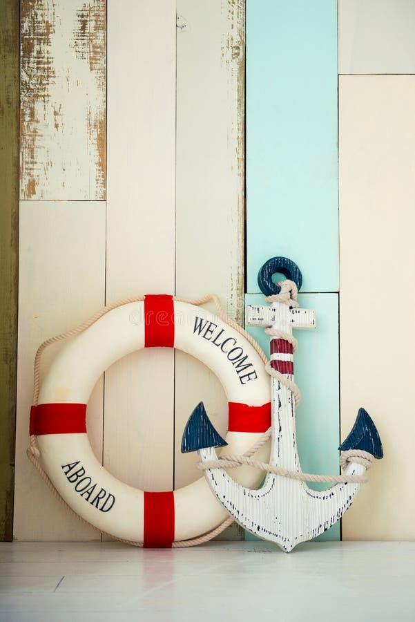 Zusammensetzung auf dem Marinethema mit Anker und Rettungsleine auf hölzernem Hintergrund lizenzfreies stockfoto