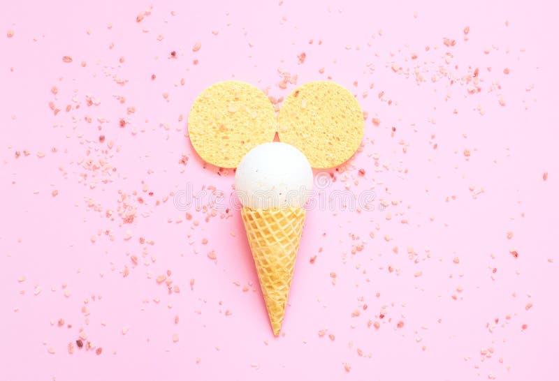 Zusammensetzung der Eistüte mit Badball auf einem hellrosa Hintergrund lizenzfreie stockbilder