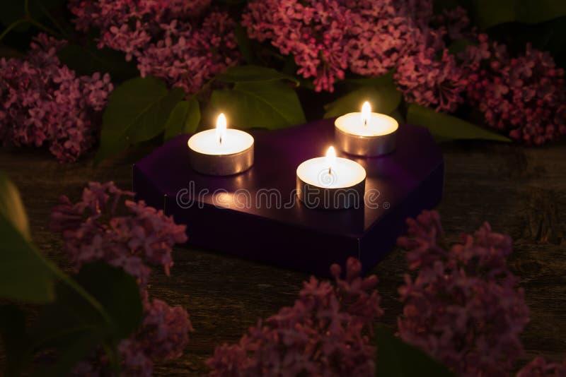 Zusammensetzung der Flieder und der brennenden Kerzen auf hölzernem Hintergrund lizenzfreies stockfoto