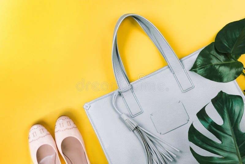 Zusammensetzung der weiblichen Handtasche, der Schuhe und des gr?nen Blattes lizenzfreie stockfotos