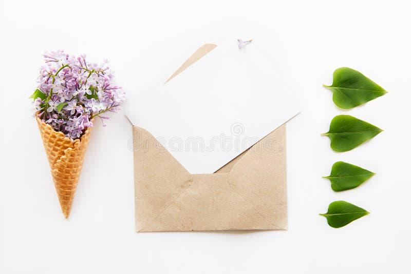 Zusammensetzung des Blumenstraußes der purpurroten lila Blumen im Waffelkegel, geöffneten im Kraftpapierumschlag mit leerer leere lizenzfreies stockfoto
