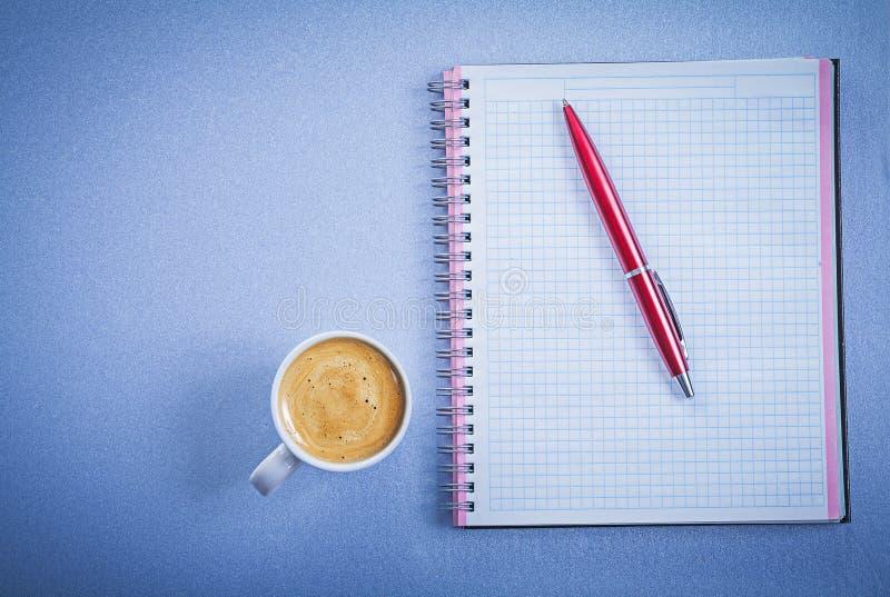 Zusammensetzung des roter Stift überprüften AnzeigenKaffeetasse-Bürokonzeptes stockfotografie