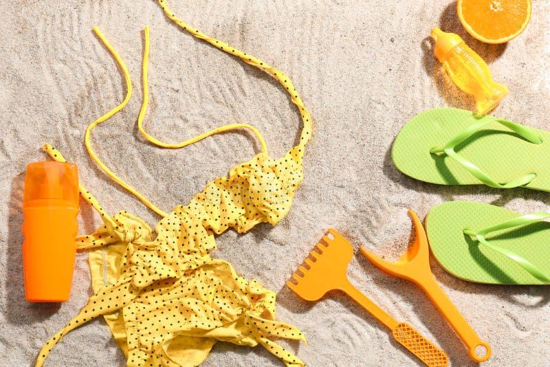 Zusammensetzung mit Badeanzug, Flipflops und Plastikspielwaren auf Strandsand stockbild