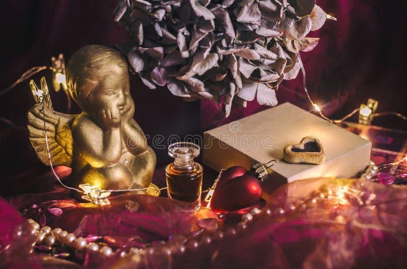 Zusammensetzung mit einem goldenen Amor, Geschenkbox, Parfüm, Hortensieblume in der mystischen dunklen Beleuchtung lizenzfreies stockbild
