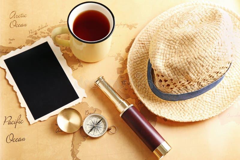 Zusammensetzung mit Fernglas, Kompass und Becher Tee auf Weinleseweltkarte Reiseplanungskonzept stockfoto