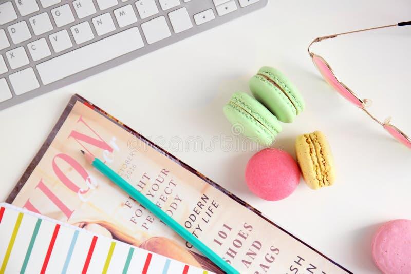 Zusammensetzung mit geschmackvollen bunten macarons, Computertastatur und Zeitschrift auf weißem Hintergrund stockfotografie
