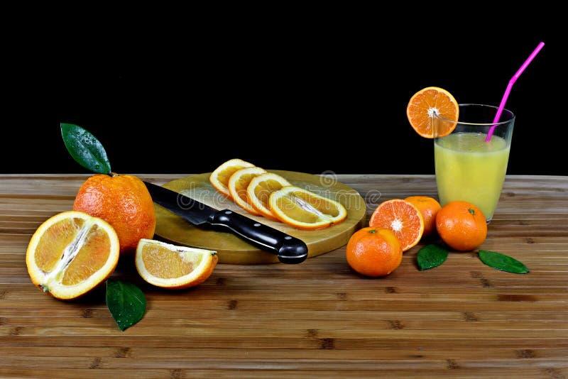 Zusammensetzung mit geschnittener Zitrusfrucht und Glas Orangensaft stockbilder